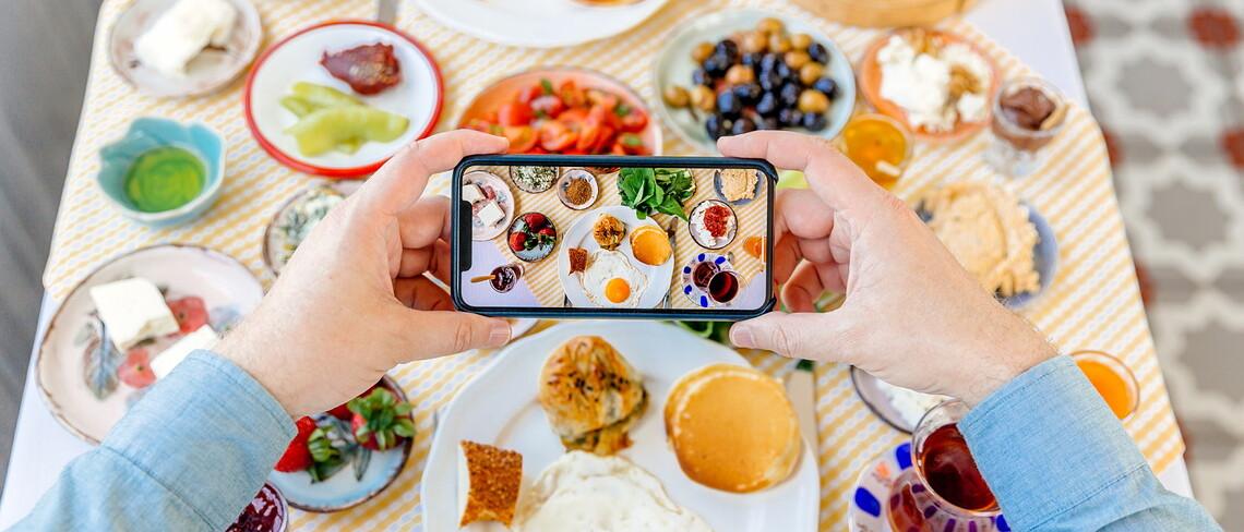 Mit einem Smartphone wird ein Foto eines gedeckten Tisches gemacht.